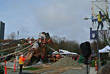 Action shot of people, wearing orange and yellow construction clothing, working to raise the Reconciliation Pole at UBC