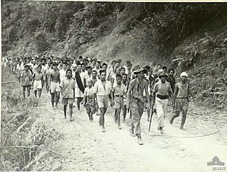 Netherlands Indies Civil Administration - Residents of Juata Village going to report to the NICA at Tarakan, after evacuation on May 9, 1945, during the Battle of Tarakan against the Japanese.