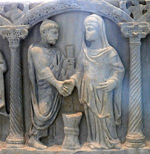 Roman couple in the ceremonial joining of hands; the bride's knotted