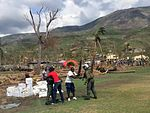 Sailors embrace Haitians after delivering aid to a landing zone. (30426927155).jpg