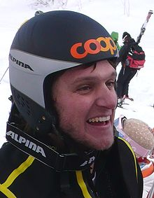 A smiling young man is geared up with a yellow-striped black winter jacket, black and gray protective helmet with orange lettering at the front, and winter goggles around his neck. He is at a snow-covered site along with other people.