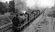 Black and white photograph of a steam engine and carriages in motion