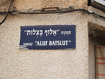 "Hebrew street sign, above in Hebrew alphabet, below in Latin letter transliteration. Aluf Batslut veAluf Shum(he) (""The Onion Champion and the Garlic Champion"") is a play by Hayyim Nahman Bialik."
