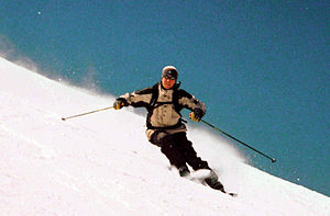 Alpine skier carving a turn on piste
