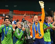 Several players are standing together with one lifting a large trophy upward