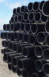 Stack of large dusty black plastic pipes.jpg