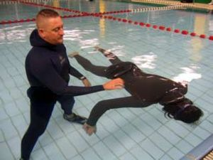 Static apnea - A diver performing static apnea face down in a pool, with the support of a partner (left)