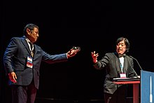 Takeshi Ikeda handling the Seiun Award prize to Takayuki Tatsumi, at the Hugo Awards Ceremony 2017 at Worldcon in Helsinki.jpg