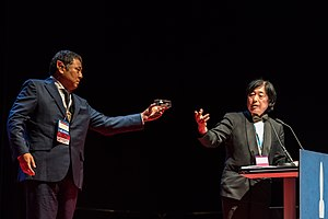 Seiun Award - Takeshi Ikeda handling the Seiun Award prize to Takayuki Tatsumi, at the Hugo Awards Ceremony 2017 at Worldcon in Helsinki.