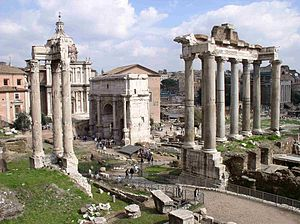 Saturnalia - Ruins of the Temple of Saturn (eight columns to the far right), with three columns from the Temple of Vespasian and Titus (left) and the Arch of Septimius Severus (center).