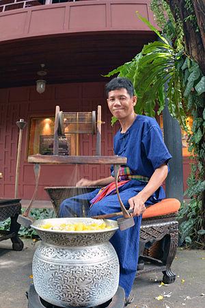 Thai silk - Thai man spools silk at Jim Thompson House