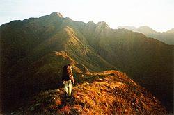 Montanhista praticando caminhada por uma trilha de cume