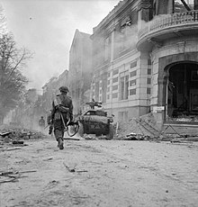 A man walks away from the camera, down a street littered with debris.  Ahead of him is a small armoured vehicle.