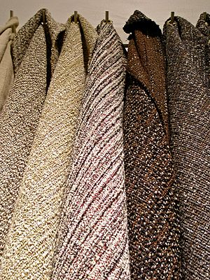 Tweed fabric hanging from hooks.