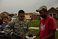 U.S. Air Force Airman 1st Class Edgar Aguilar, center, with the 963rd Airborne Air Control Squadron, serves food to people affected by a tornado May 23, 2013, in Moore, Okla 130523-F-RH756-148.jpg