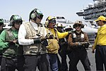 U.S. Navy Aviation Boatswain's Mate (Handling) 1st Class Cameron Fisher, center, instructs Sailors during an aircraft firefighting drill aboard the aircraft carrier USS Nimitz (CVN 68) June 23, 2013, in 130623-N-RX668-286.jpg
