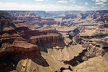 Wide canyon with steep tan colored walls. A river inside a valley is below a broad gently sloping surface.