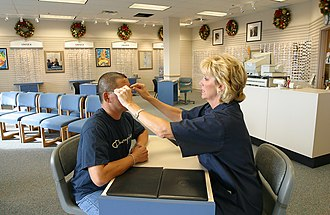 Optician - A US Navy optician adjusting a customer's glasses