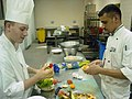 US Navy 041013-N-0180W-005 Radisson Chef instructs a Culinary Specialist Seaman Rodney Smith, left, on garnishing techniques as part of a Task Force Excel (TFE) Program.jpg