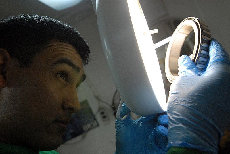File:US Navy 060622-N-2959L-191 After cleaning an aircraft tire bearing, Aviation Structural Mechanic 3rd Class Jose Martinez-Deleon inspects the bearing to ensure there is no damage before putting the tire back together.jpg