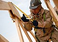 US Navy 071221-N-3857R-007 Builder 3rd Class Adam Turbeville, assigned to Naval Mobile Construction Battalion (NMCB) 1, connects his safety harness to a truss while working on the construction of a fellowship hall.jpg