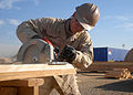 US Navy 100106-N-9564W-238 Builder Constructionman Dennis Dardono cuts wood for the construction of a Southwest Asia hut in the expansion area of Camp Leatherneck.jpg