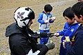 US Navy 110321-N-IC111-219 Naval Air Crewman 2nd Class Chris Tautkus hands treats to Japanese children during a humanitarian assistance mission.jpg