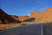 Highway following the right side of a narrow canyon with a long shadow cast from the left.