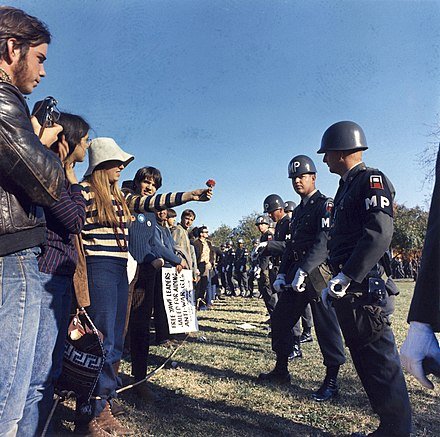 "A demonstrator offers a flower to military police guarding the Pentagon during the National Mobilization Committee to End the War in Vietnam's 21 October 1967 ""March on the Pentagon"" Vietnamdem.jpg"