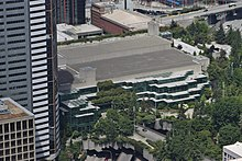 An aerial view of a concrete building with a bare roof and several terraced glass walls, abutting a park full of trees between several high-rise towers