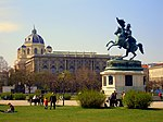 A large statue depicting a soldier riding a horse stands in the middle of a park.