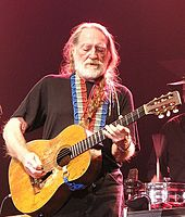 A man with long white hair and white beard playing a guitar. He wears a black T-shirt, which is crossed by the red, white and blue strap of the guitar. He also wears black pants.