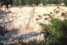 Gathering of people at top edge of sinkhole appear tiny compared to sloping sides of sinkhole about 70 feet deep and a few hundred feet across. Debris is scattered on slope and floating in dirty water in bottom of sinkhole.