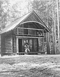 Woman sitting on porch of log cabin, unidentified location, August 14, 1908 (SARVANT 55).jpeg