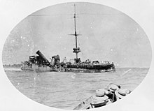 A badly damaged ship sits in the water, while in the foreground sailors in another vessel watch on.
