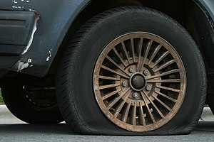 English: A flat automobile tire. Français : Un...