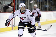 "A female ice hockey player is skating towards the camera.  Her jersey is white and features a stylized ""USA"" on the front."