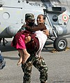 A Nepalese Army Officer helping a stranded woman evacuated by an Indian Air Force (IAF) MI-17 V5 helicopter following a recent earthquake in Nepal.jpg