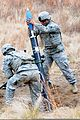 "A U.S. Army mortarman hangs an 81mm mortar training round into an M252 81 mm mortar system and waits for the command of ""fire"" 121212-A-ZZ999-128.jpg"