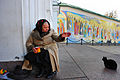 A beggar woman against the background of Saint Sophia's Cathedral fresco paintings. Kiev, Ukraine, Eastern Europe.jpg