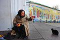 A beggar woman against the background of Saint Sophia's Cathedral fresco paintings. Kiev, Ukraine, Eastern Europe.jpg