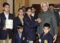 "A group of orphaned and destitute children pinning the flag to the Vice President, Shri Mohd. Hamid Ansari, on the occasion of 'Flag Day' to observe the ""Communal Harmony Campaign and fund raising Week"" in New Delhi.jpg"