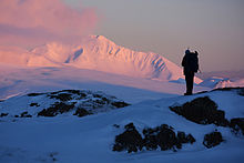 A hiker standing on a rocky knoll, the pink early morning light illuminating snow-covered Mt. Moffett in the background