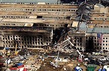 Aerial view showing damaged, burned, and  collapsed portion of the Pentagon with firefighting and rescue equipment  nearby