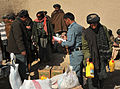 Afghan National Police and coalition special operations forces food handout 120207-N-UD522-055.jpg