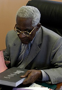 An image of Aimé Césaire in 2003 on a desk reading the cover of a book.