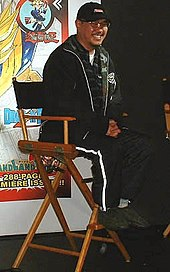 Akira Toriyama sitting on a chair smiling wearing black clothing with glasses and chin facial hair.