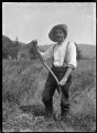 Albert Percy Godber holding a scythe, clearing a section at Pinehaven. ATLIB 288144.png