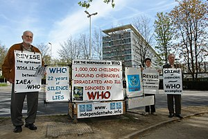 Chernobyl: Consequences of the Catastrophe for People and the Environment - Yablokov (left) and Vassili Nesterenko (farthest right) protesting in front of the World Health Organization (WHO) headquarters in Geneva, Switzerland in 2008.