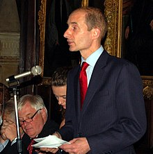 A balding man in his 40s, with close-cut brown hair, wearing a suit with a red tie, speaks into a microphone with papers in his hands